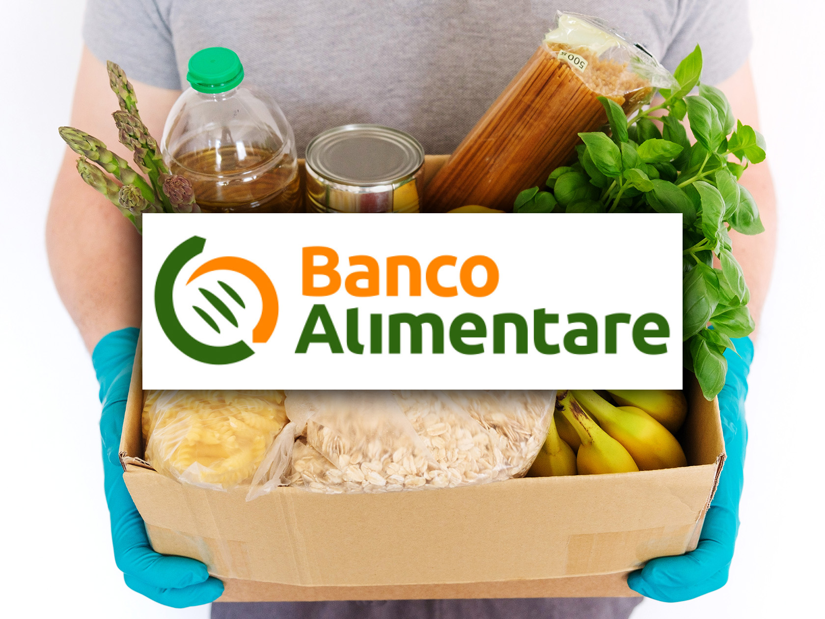 Male hands in medical rubber gloves hold a cardboard box with products. Sunflower oil, canned food, pasta, oatmeal, rice, vegetables and fruits. Food Delivery, Food Donation